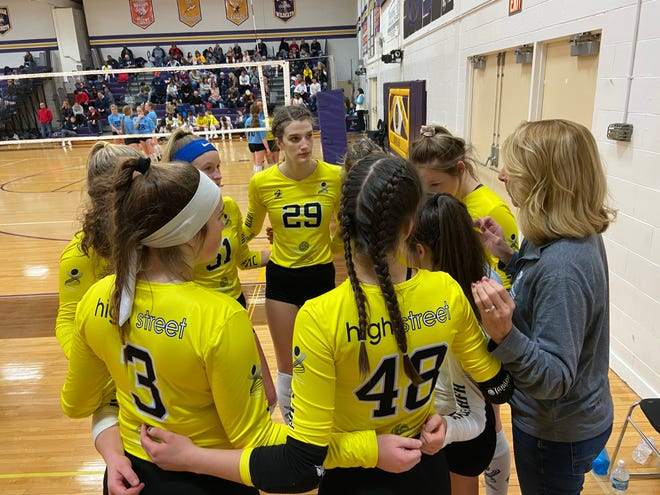 The High Street Athletics volleyball team huddles up during a match in early 2020 at Blissfield High School.