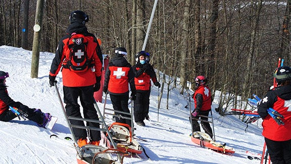 Members of Swain Ski Patrol practicing a first aid scenario on the hill. These red-coated volunteers are seeking new candidates to join the National Ski Patrol.