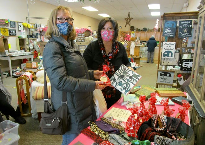 """Cold temperatures did not keep shoppers away from the """"Pop Up"""" Farmer's Market on Saturday at businesses in downtown Geneseo. Among the shoppers was Cynthia Wells Geneseo, who looked at the art work and candies offered for sale from Lori Gotthardt, Rock Island, a vendor at My Moon Creations. Gotthardt also offers head bands at her business, """"me & mom."""""""