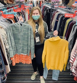 An employee showcases clothes at Plato's Closet in Muskegon. Judy Bradford, owner of the Muskegon storefront, will open a second Plato's Closet location in Holland Township on West Shore Drive. The location is already open to sellers.
