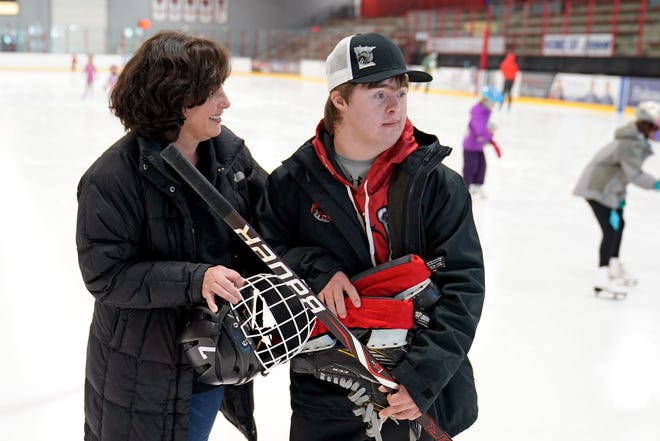 Suzy Lindeberg poses with her 20-year-old son, John, on a hockey rink Feb. 9, 2021 in Stillwater, Minn. John, who has Down Syndrome, can't spend as much time at the rink as he used to since he is at higher risk for hospitalization or death if he caught COVID-19, but his mother and other advocates worry that the state of Minnesota has placed people with disabilities too far down the priority list. (AP Photo/Jim Mone)