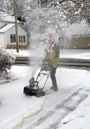 Snow flies into the air from the Earthwise electric snow thrower.