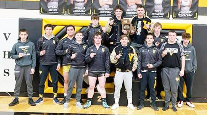 The Versailles boys wrestling team celebrates a second straight district team title on February 13 in Versailles. The Tigers had five district champions and sent 12 wrestlers overall to sectionals.