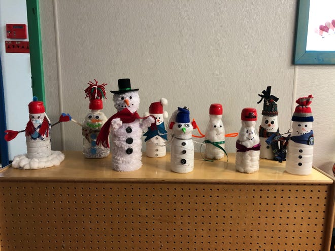 Families at Jack 'n' Jill Child Care use household items to create snowmen for residents of Atria Senior Living in Greece.