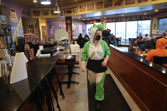 "Mihlan Fiore heads back to the kitchen to grab an order  during ""Onesie Sundays"" at J&M Diner in Framingham, Feb. 14, 2021. On ""Onesie Sundays,"" customers come in, dressed in onesies, and whoever has the best outfit wins a gift certificate."