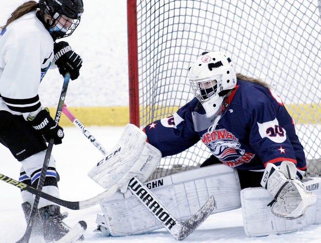 Medway/Ashland goalie Jenna Shutt, a Holliston High senior, makes a stop on Hopkinton's Kelly Bailey (left) during a hockey game at New England Sports Center in Marlborough on Feb. 14.