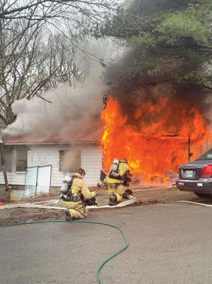 Two Oak Ridge firefighters battle a house fire on Jellico Lane in the city on Saturday afternoon. Two people living at the home were displaced.