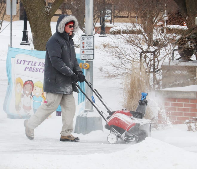 Mick Peterson cleans the snow off the sidewalk in front of St. Mary's Catholic Church Monday morning. More snow was expected Monday evening.