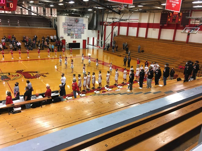 The Pekin boys basketball team stands for the national anthem in Hawkins Gym before the Dragons' opening night game against Morton.