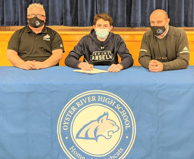 Oyster River High School senior Hayden Marshall, center, sits with boys lacrosse coach Ruppy Hailey, left, and athletic director Andy Lathrop last week when he signed his National Letter of Intent to play men's lacrosse at Saint Anselm College.