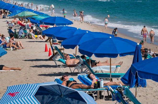 Beachgoers soak up the sun as temperatures soared into the mid 80's Monday in Lake Worth Beach.