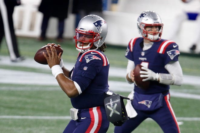 Patriots quarterbacks Cam Newton, left, and Jarrett Stidham warm up before a game against the Buffalo Bills in December. Their struggles on the field were key factors in the team finishing 7-9 and missing the playoffs.