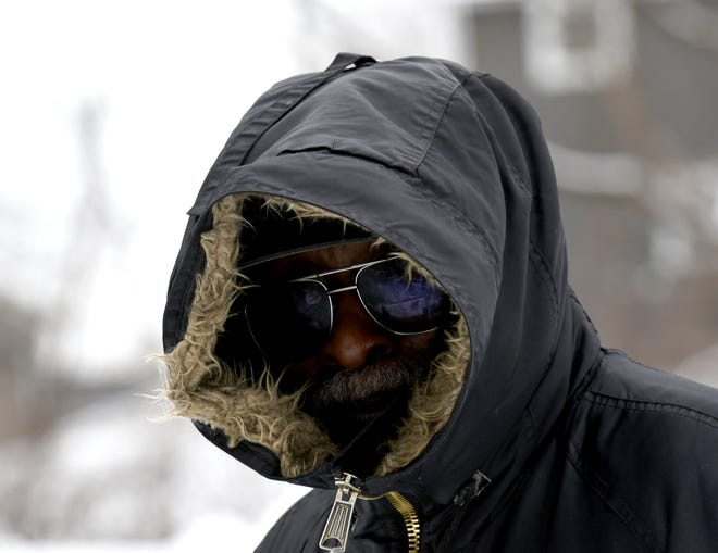 Sherman Smith of Massillon bundles up as he walks his dog at Reservoir Park in Massillon on Monday,