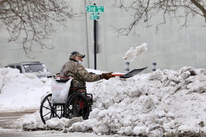 A man shovels snow and ice away from the sidewalk at Third Avenue and Seventh Street on Monday, Feb. 15, 2021, in downtown Rockford. Temperatures were double digits below zero in Rockford with the wind chill factor.
