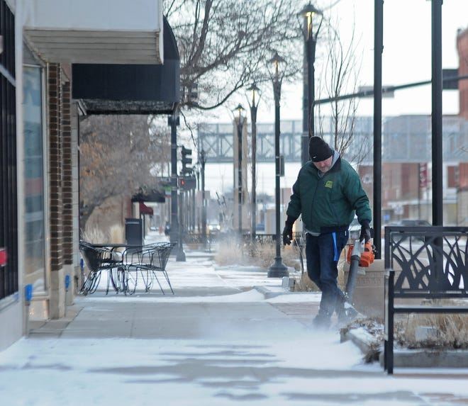 """Shawn Copeland, executive director of The City Teen Center, uses a leaf blower to blow the snow off of the sidewalk of a building on the 100 block of N. Santa Fe Avenue early Monday with the temperature at minus 8 degrees. """"It is pretty chilly, there has been lots of closings and not much going on around here,"""" Copeland said."""