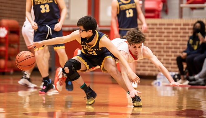 Stephenville's Kelvin Ong (21) fights for a loose ball with Glen Rose's Kolton Mooney on Friday night at Tiger Arena.