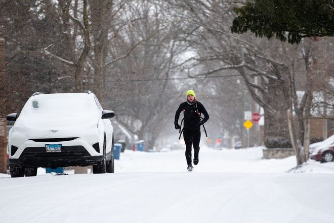 """Rev. Dominic Rankin heads down South Feldkamp Avenue on a morning run with temperatures right at zero in Springfield, Ill., Monday, February 15, 2021. """"Good, chilly but glad to get out,"""" said Rev. Rankin of his morning run. """"It's beautiful with the snow."""" [Justin L. Fowler/The State Journal-Register]"""