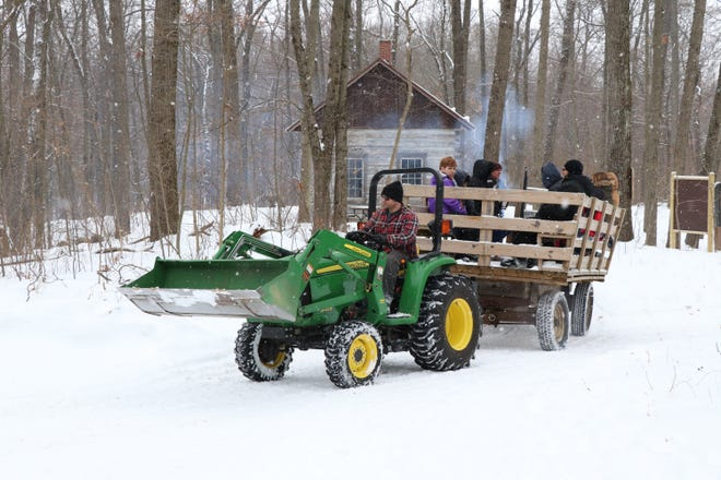 """Camp Fort Hill volunteer Ryan Franks takes a wagon of visitors on a tour of the wooded property Saturday at """"Winter Adventure."""""""