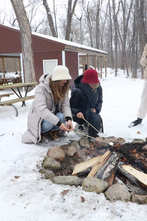 """Visitors toast a S'more on an open campfire Saturday at Camp Fort Hill's """"Winter Adventure."""""""