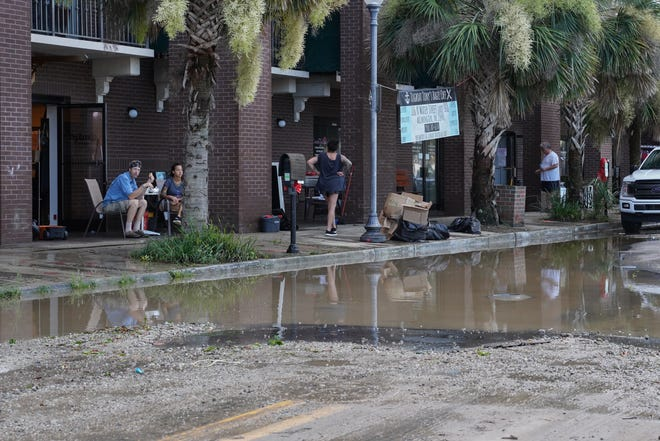 Business owners and residents cleaned mud and floodwaters from their riverfront properties on Aug. 4, 2020, after Hurricane Isaias brought a record 9-foot storm surge to downtown Wilmington.