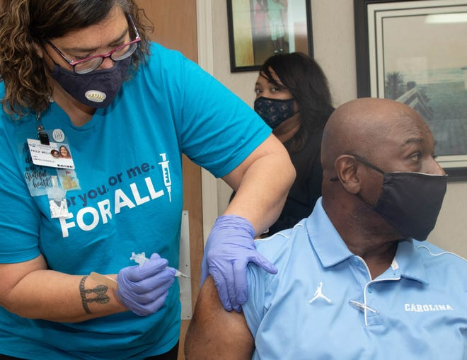 Former UNC basketballer Phil Ford receives his COVID vaccination from CarolinaEast LPN Paula Wells.