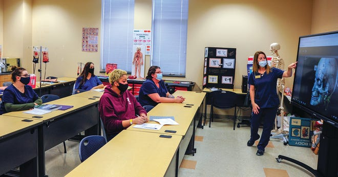Pamlico Community College Medical Assisting Instructor Tina Hardison, standing at right, uses a smartboard to show the anatomy of the human skull. Hardison is a 2015 graduate of the program. [CONTRIBUTED PHOTO]