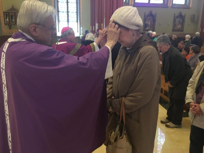 Monsignor Anthony Rosaforte places ashes on Yantic resident Carol Kingsley on Ash Wednesday, Feb. 26, 2020, at the Cathedral of St. Patrick in Norwich.
