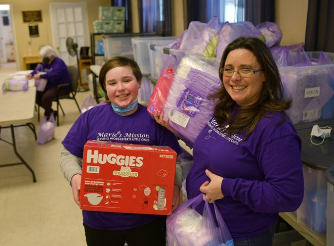 Sarah Galvin and her son, James, 11, hold diapers available through Marie's Mission, the diaper bank program which helps about 75 families in need. The program is housed in Tatro Hall behind St. Michael's on the Heights Episcopal Church in Worcester.