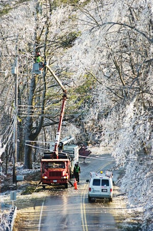In the aftermath of the Dec. 11-12, 2008 ice storm, a crew trims tree limbs resting on utility lines along Route 56 in Rutland.