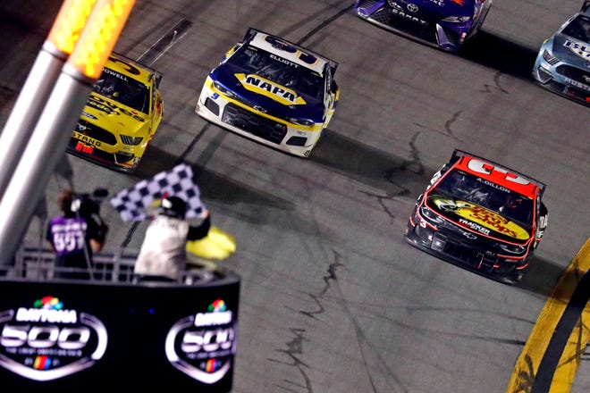 Michael McDowell (left) takes the checkered flag at the Daytona 500 just ahead of Chase Elliot (middle).
