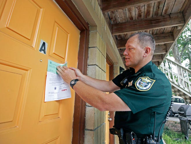 Alachua County Sheriff's Deputy Scott Caley tapes an eviction notice on the front door an apartment several years ago. An eviction resistance network in Alachua County that is part of the Alachua County Labor Coalition is working with tenants to help with the current eviction crisis caused by job loss during the COVID-19 pandemic. [File Photo by Matt Stamey/Special to The Guardian]