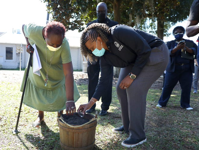 Evelyn Foxx, left, president of the local NAACP, and Gigi Simmons, right, Gainesville City Commissioner representing District 1, take small glass jars of soil from a bucket of soil from the ground last Thursday at Haisley Lynch Park during a soil collection ceremony as part of the truth and reconciliation process recognizing the horrific lynchings that occurred in Gainesville. Local officials and community partners gathered for the event that traveled to six locations around the city to collect soil from areas that are both known lynching sites and some that are symbolic sites.  [Brad McClenny/Special to The Guardian]