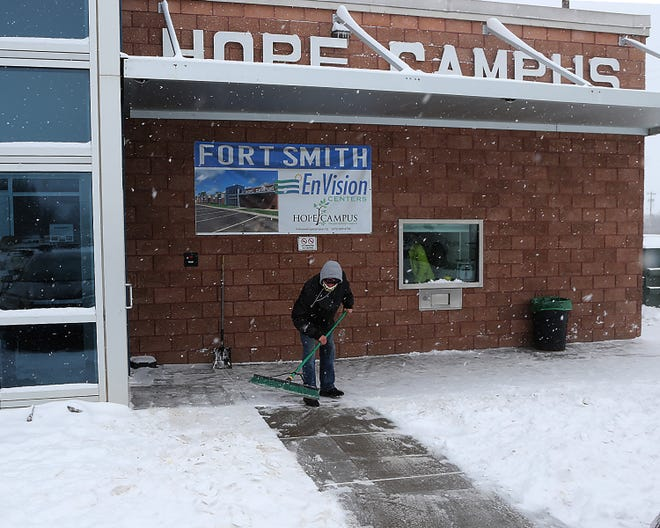 Brandon Becker sweeps snow from the Hope Campus front doors and sidewalks, Monday, Feb. 15, at the 301 South E St. facility. Chris Joannides, MSW, executive director said that the homeless shelter provided sleeping arrangements for 128 people, Sunday, Feb. 14, after the outside temperature dropped to single-digits and a heavy snow blanketed the area.