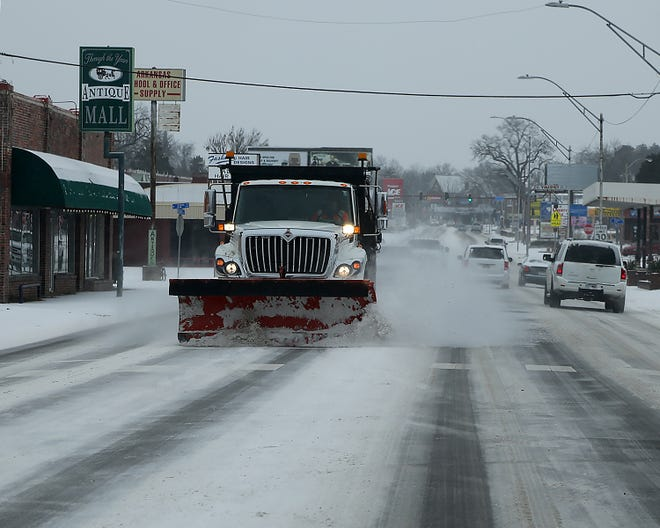 A Fort Smith Street Department dump truck is fitted with a grader to remove snow from Rogers Ave, Monday, Feb. 15, in Fort Smith.