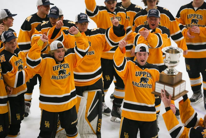 Upper Arlington players celebrate defeating St. Charles 3-2 in the CBJ Cup championship game Feb. 14 at OhioHealth Ice Haus.