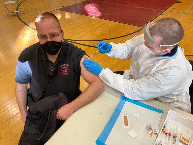Chris Pouliot of the Lexington fire department receives the second dose of his COVID-19 vaccine.