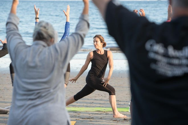 Angela Warren Ippolito, whom the Swampscott Reporter columnist Ina Resnikoff profiles in this week's edition, directing a yoga class on Eisman's Beach during summer months.
