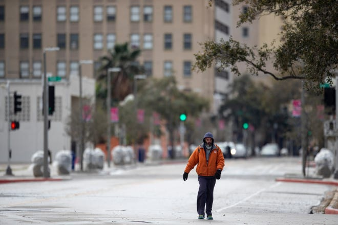 A man walks down Water Street in freezing temperatures on Monday, Feb. 15, 2021.