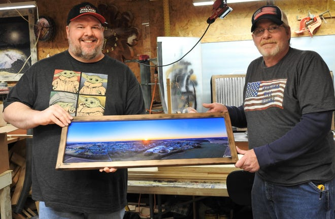Kyle Dobbins and Jay Lenhart hold a drone photo of West Lafayette in a custom frame that will be donate to an auction to help fund a K-9 unit at the West Lafayette Police Department. They two joined forces about a month ago to offer frame prints.