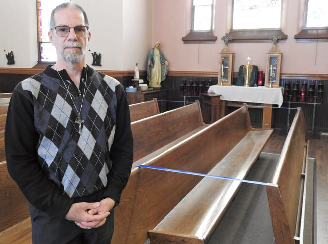 Deacon Doug Mould of Sacred Heart Catholic Church at a pew, blocked off to allow social distancing, and the Tabernacle in the background. Ash Wednesday services will look differently across the country this year because of the COVID-19 pandemic.