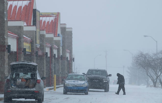 A shopper makes his way through the snow to Ruler Foods in Newburgh, Ind., Monday morning, Feb. 15, 2021. The second round of snow had just started and was expected to continue through the afternoon.