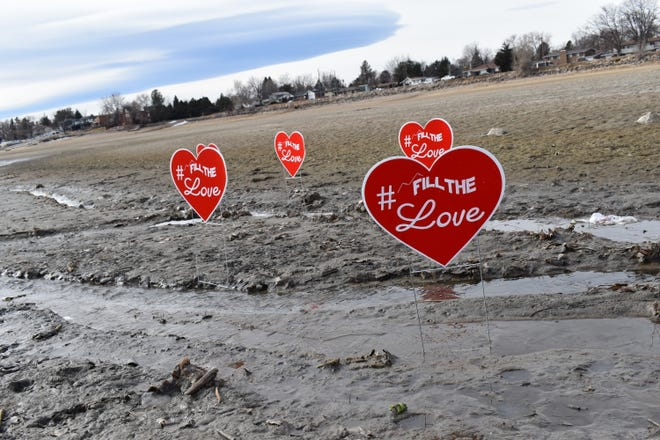 Fill the Love signs stick out of the muddy and empty shores of Lake Loveland near the lake's north shore swim beach.