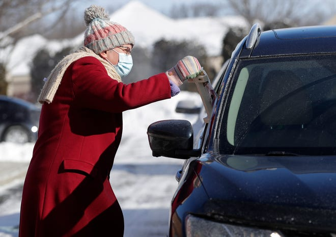 Ascension Lutheran Church Pastor Lori Swenson gives a packet with ashes for Ash Wednesday and other items for Lent to a parishioner during a drive-through pick-up  on Feb. 14, 2021, in Allouez, Wis.