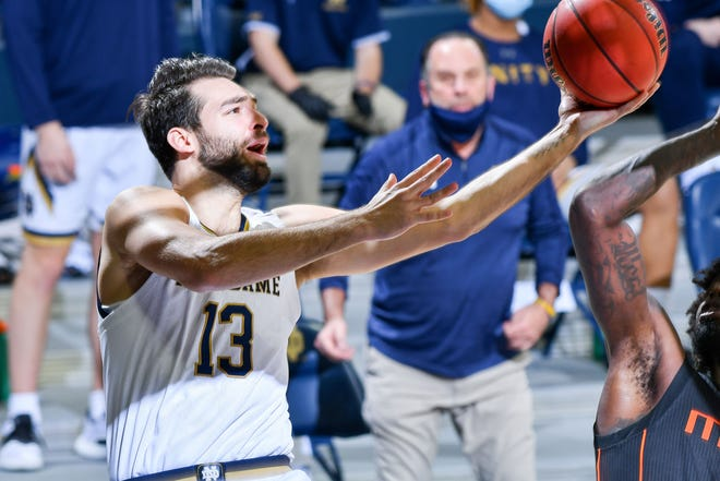 Feb 14, 2021; South Bend, Indiana, USA; Notre Dame Fighting Irish guard Nikola Djogo (13) goes up for a shot in the second half against the Miami Hurricanes at the Purcell Pavilion.