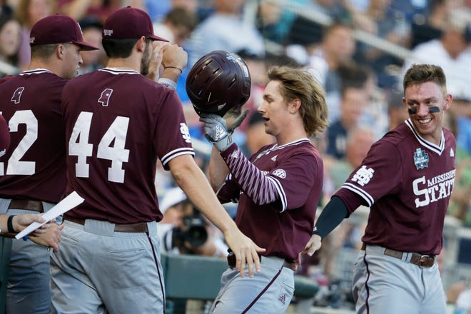 Mississippi State's Rowdey Jordan, second from right, is greeted at the dugout after scoring on a single by Gunner Halter in the fourth inning of an NCAA College World Series baseball game against Louisville in Omaha, Neb., Thursday, June 20, 2019. (AP Photo/Nati Harnik)