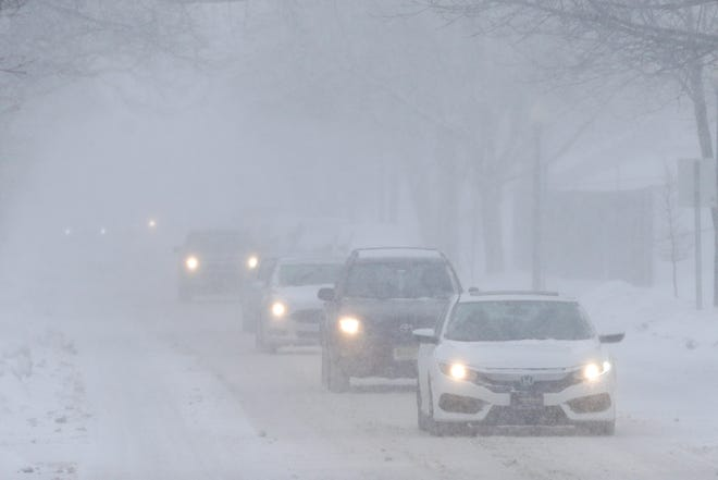 Cars drive along in the snow.