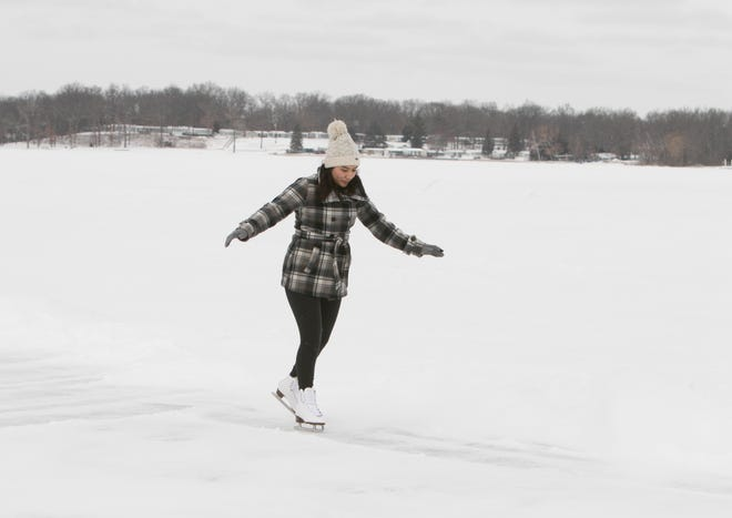 Genoa Township resident Kaylena Banghart gets acclimated to skating on Lake Chemung, having brought a snow shovel out to clear a patch of ice Monday, Feb. 15, 2021 as she learns to skate.