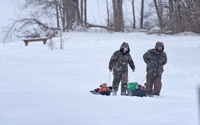 After hauling six perch out of the Clear Fork Reservoir ice fishing  Monday morning, Jay and Lisa Broomfield drag their gear through the snow back to their vehicle.