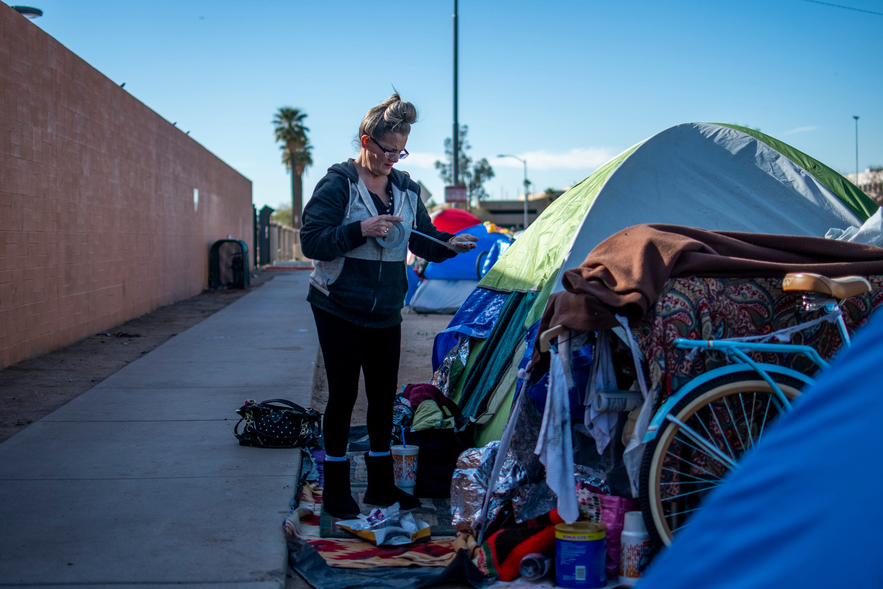 Darlene Carchedi makes a lint roller out of duct tape outside her tent in downtown Phoenix on Jan. 3, 2020. She says that when officials clean up homeless encampments, the trauma of being homeless repeats itself.