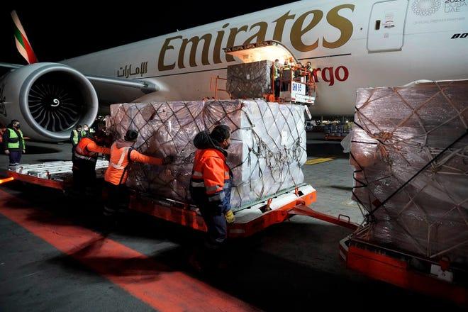 Fotografía cedida hoy por la Presidencia de México, donde se observa a personal aeroportuario mientras descarga un lote de vacunas de AstraZeneca contra la covid-19, en el Aeropuerto Internacional Benito Juárez de la Ciudad de México.